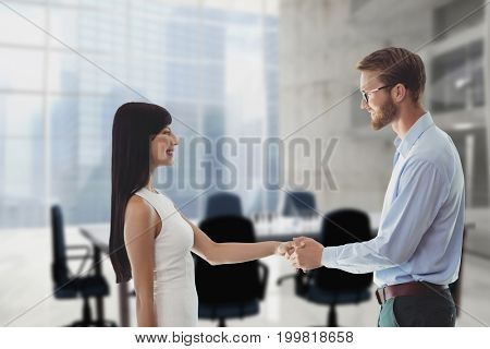 Digital composite of Happy business people shaking hands against office background