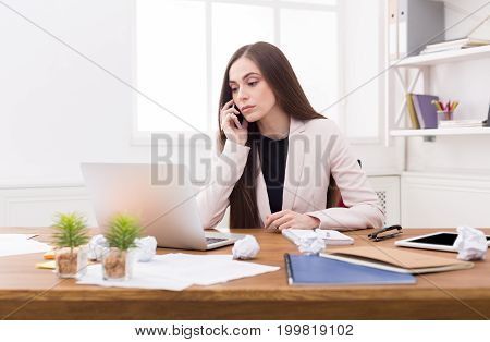 Serious business woman at work talking on phone, sitting at her working place in office, copy space