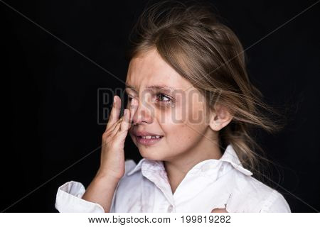 Child abuse. Sad and lonely girl crying . Injured child posing as victim of domestic violence
