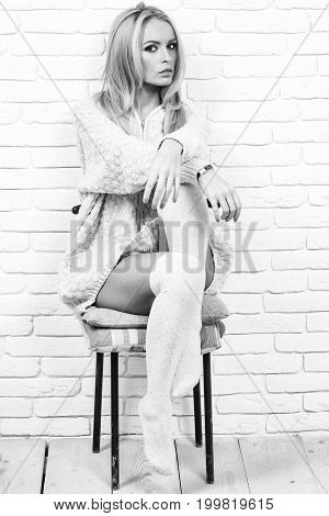girl or beautiful cute woman fashion model with blond hair in sexy knitted sweater sits on chair on brick wall black and white