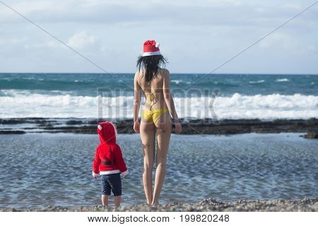 Woman and child standing on sea beach. Mothers day and family love. Winter holidays concept. Christmas and new year celebration. Girl in swim suit and boy wearing santa costume.