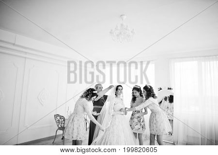 Bridesmaids And Mother Helping Bride To Dress Up And Get Ready For Her Wedding. Black And White Phot