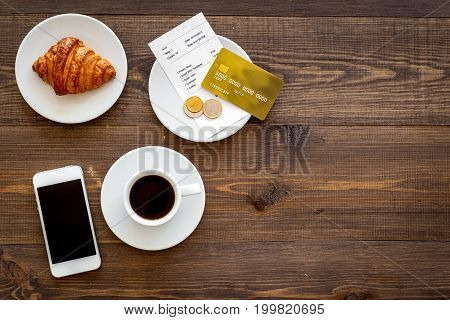 Pay bill at cafe by card. Bill and bank card near coffee and croissant on dark wooden table top view.