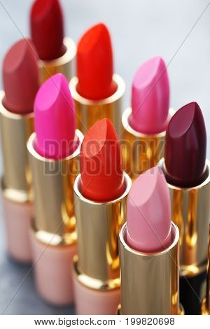Colorful lipsticks on the grey wooden table