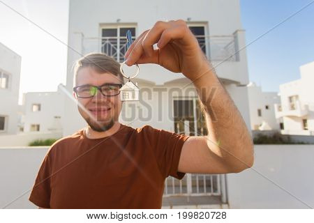 Happy young man showing off the key to his new home. Owner, real estate and people concept.