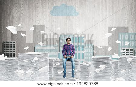 Attractive man in casual clothing sitting among flying paper planes with sketched cityscape view on background. Mixed media.