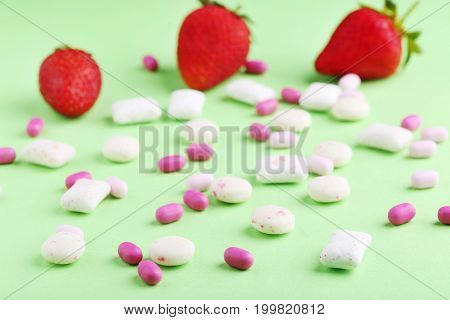 Chewing Gums With Strawberries On Green Background