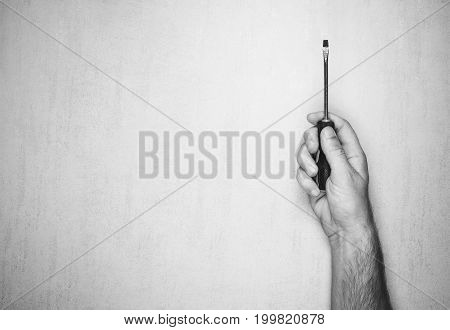 Screwdriver in a man's hand on a gray background top view. black and white photo. mock up for text phrases lettering