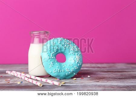 Tasty Donut With Sprinkles And Bottle Of Milk On Wooden Table