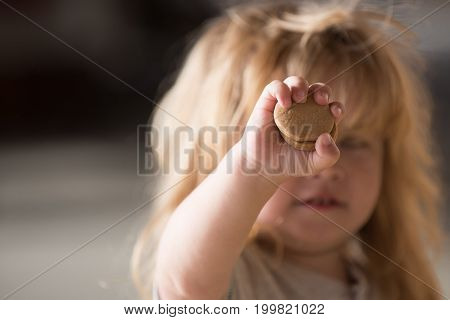 Childish hand with tasty biscuits holding by fingers of small boy kid with cute face long blond hair on blur background childhood and happiness concept