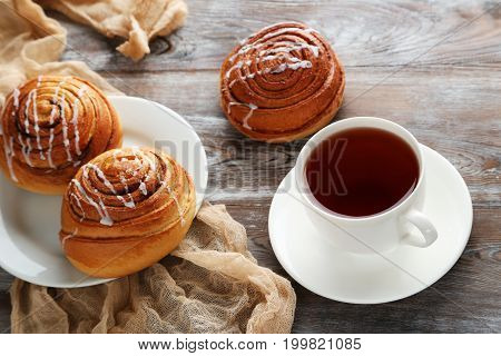Cinnamon Buns With Cup Of Tea On Wooden Table
