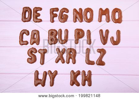 Chocolate Cookies Alphabet On Pink Wooden Table