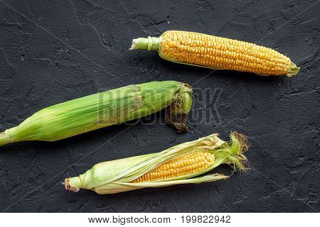 Vegetarian food. Corn cobs on black stone background top view.