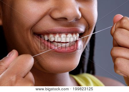 African female taking care of her teeth using dental floss