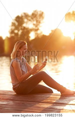 Woman looking at cellphone on dock and refreshes with drink at sunset
