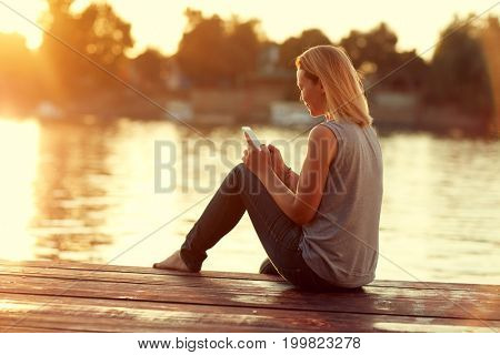 Girl with cellphone sitting on dock near river on sunset