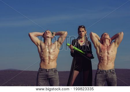 Woman with baseball bat and men. Group of people on blue sky. Bandit gang have conflict. Beauty and fashion. Men and sport or criminal girl outdoor.