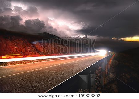 A mountain asphalt road with a passing car on the sunset to the right and a thunderstorm with lightning from the left is shot on a long exposure.