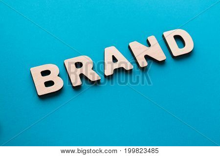 Word Brand on blue background. Famous name, trendy goods, tendency concept