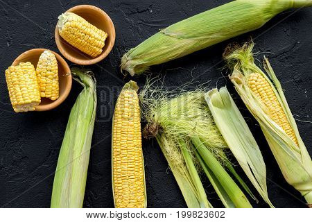 Organic farm food. Cutted corn cobs on black stone background top view.