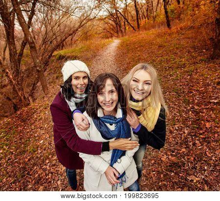 Smiling happy women enjoying walk in autumn forest