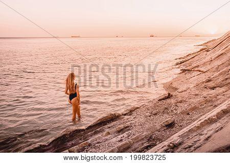 Pretty blonde woman in black swimwear posing on sea with warm sunset colors.