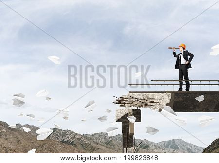 Engineer in suit and helmet looking in spyglass while standing among flying paper planes on broken bridge with skyscape and nature view on background. 3D rendering.