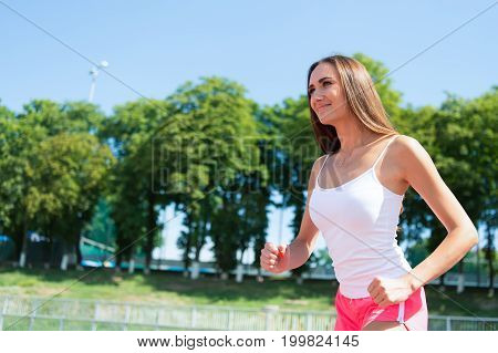 Woman Running On Arena Track.