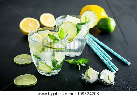 Refreshing citrus lemonade cocktail with crushed ice and lame with lemon on dark background
