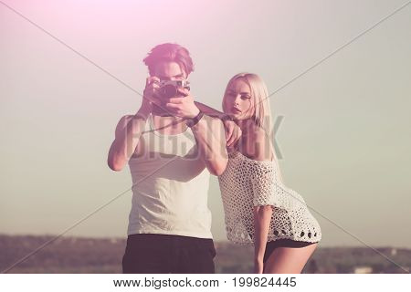Couple in love and romance. Man with muscular body with girlfriend. Girl with photographer outdoor. Guy with photo camera on athletic chest. Beauty and art fashion.