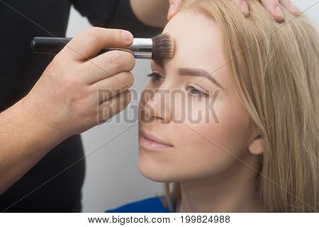 Hand With Makeup Brush Applying Powder On Girl Face