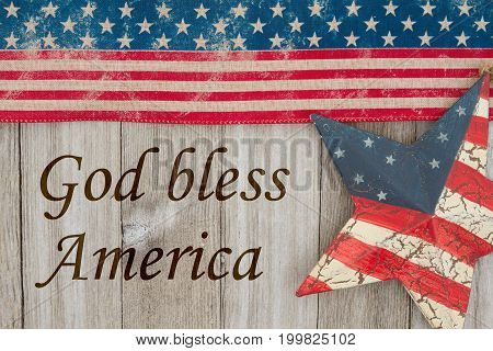 America patriotic message USA patriotic old flag and a star and weathered wood background with text God Bless the USA