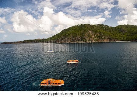 St. Barts France-November 25. 2015: Sail and orange boats sailing on sea water in France on sunny day on mountain landscape background. Summer vacation. Vessels and marine travelling concept