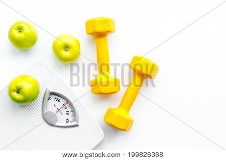 Sport and diet for losing weight. Bathroom scale, apple and dumbbell on white background top view.
