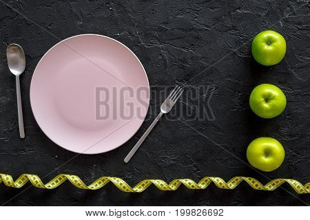 Slimming diet. Apple at plate on black background top view.