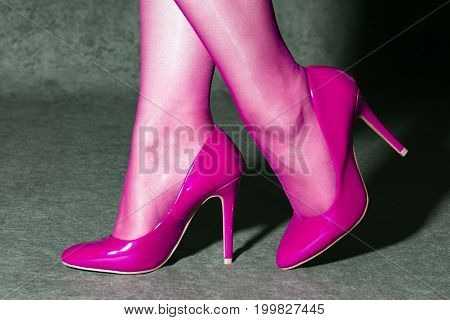 Female legs in pink socks and pink high heels shoes.
