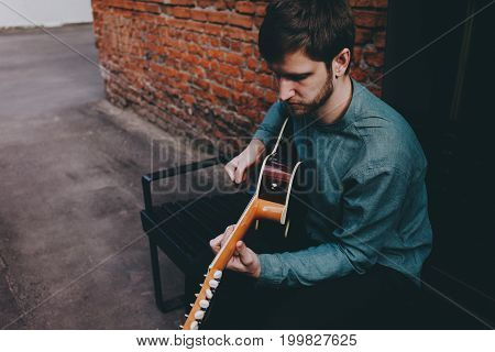 Hipster musician playing guitar on brick wall background.