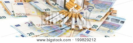 20 and 50 Euro banknotes bills cash with cigarettes. Concept of cost of tabacco cigarettes. Front and top view close-up. Panormamic picture