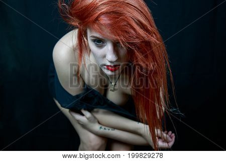 Portrait of woman with makeup posing while undressing and bending forward on black background.