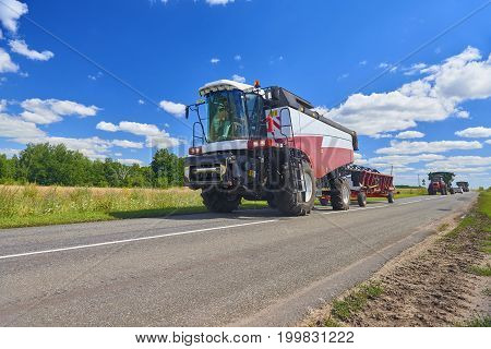 View on red white wheat harvester combine machine going to harvest wheat rye bread-corn around gold wheat fields in summer. August wheat harvesting in Russia, Europe. Rye harvester on road, blue sky