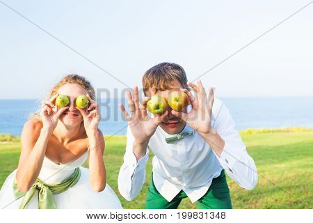 April fools day concept - Young wedding couple funny portrait with apples.