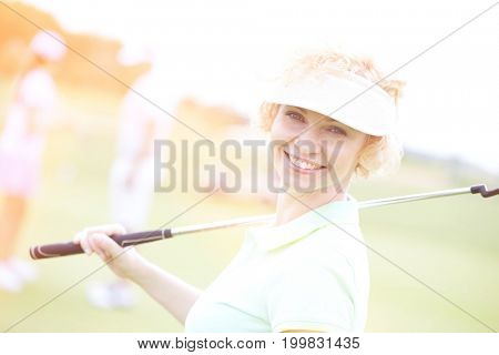 Portrait of happy female golfer holding golf club