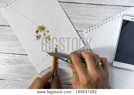 Man Sharpens A Pencil With A Knife In The Workplace. Texture And White Background.