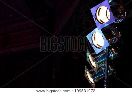 Close view on four big metal reflector lamps for making the light on concert stage