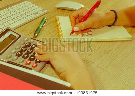 female putting his ideas and writing business plan at workplacewoman holding pens and papers making notes in documents on the table in office. Business and finances concept - Retro color