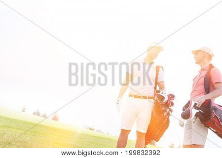 Male friends conversing at golf course against clear sky on sunny day