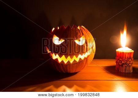 Spooky smiling halloween pumpkin with burning fire candle flame. The big helloween symbol has a mad face glowing eyes mouth and teeth glow. Black orange nightmare of October 31st on wooden table.