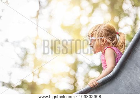 Close-up image with a little girl having fun on a slide from a playground on a sunny day.