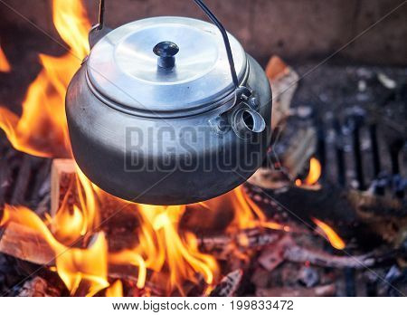 Metallic coffee pot in campfire heat. Wood burning with flames beneath the pot.