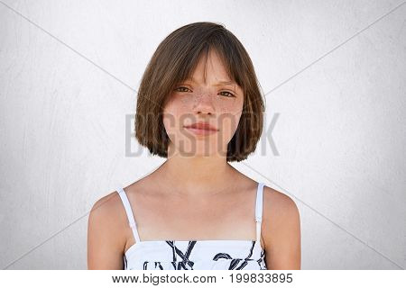 Freckled Girl With Hazel Eyes And Dark Short Hair, Looking With Displeasure Into Camera While Posing